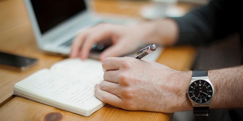 Ein Mann macht sich Notizen, um sich zu merken, wie er seine Website für Google optimieren kann.