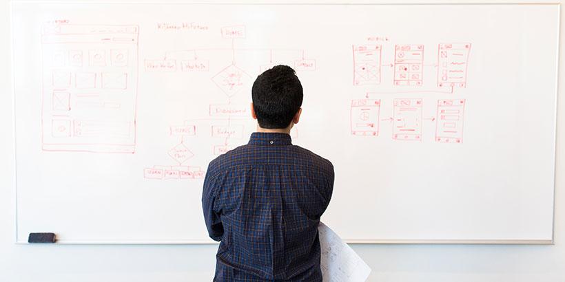 Ein Mann steht vor einem Whiteboard, an dem eine Website Struktur skizziert ist.