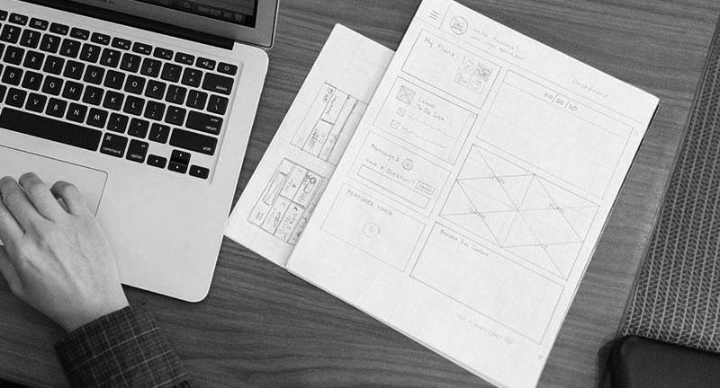 Blätter mit skizzierten Wireframes für das Konzept einer Website Struktur, mit einem Laptop daneben.